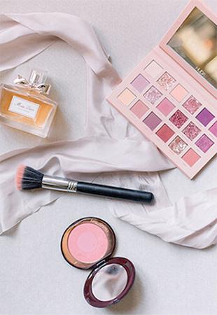Overhead Shot of Dior Perfume, Charlotte Tilbury Blush, Huda Beauty Makeup and Perfume