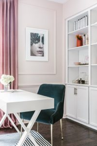 Beautiful Blush Studio with Stlyed Shelves Containing High End Beauty Products, Desk and Velvet Chair