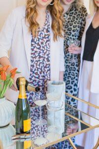 Three Brightly Attired Women, One Woman Pours Veuve Clicquot into Champagne Glasses