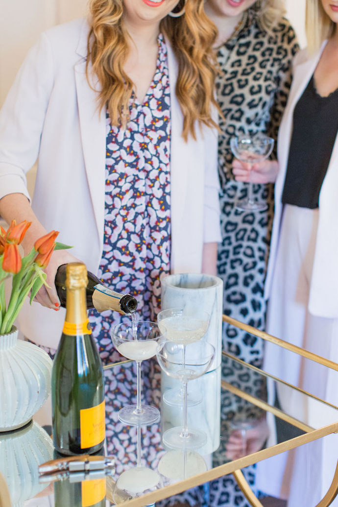 Three Brightly Attired Women, One Woman Pours Veuve Clicquot into Champagne Glasses