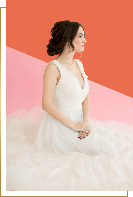 Woman in Bridal Gown Poses on Pink and Choral Background with Low Coiffed Updo with Soft Wavy Tendrils