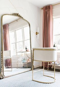 stylish chair next to large floor-length mirror