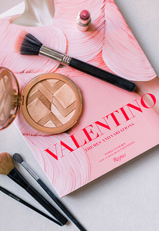 Overhead Shot of Guerlain Bronzer, Makeup Brushes and Valentino Book
