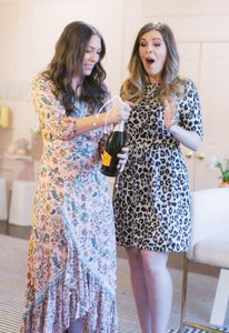 two women opening a bottle of champagne