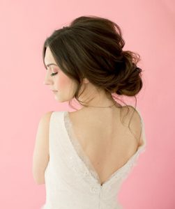 Brunette model posing against pink background with rounded bun and slight bouffant