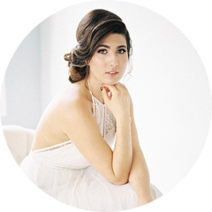 dark-haired women with Low, Voluminous Updo posing against white background
