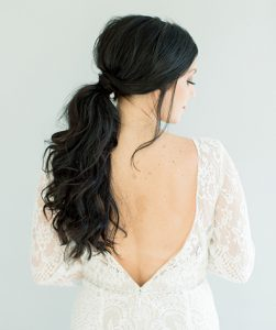 Model shot from behind with sideswept long ponytail. Side part and loose hair adds romantic look.