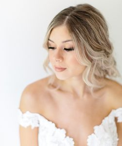 Model in Wedding Gown with Loose Hair coming out of lovely bun