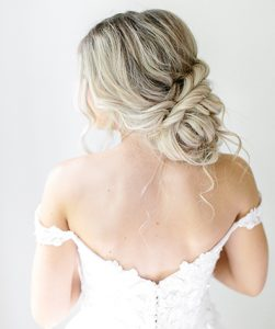Model in Wedding Gown with Blonde Locks Loosely pulled into twisted low bun with soft tendrils coming out of bun