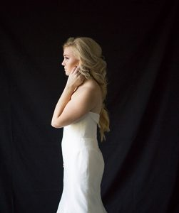Blonde Model in wedding gown shot from side long fishtail braids loosely pulled together