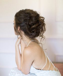 Brunette Model with Tousled updo and loose tendrils falling out of bun
